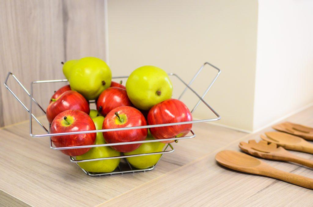 Em uma mesa, uma fruteira com maças vermelhas e verdes.