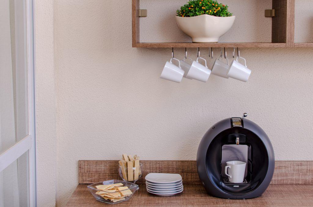 Na imagem, uma cafeteira com bolachas e pires. Ainda, em cima, xícaras em um porta-xícaras e uma planta em um prateleira.