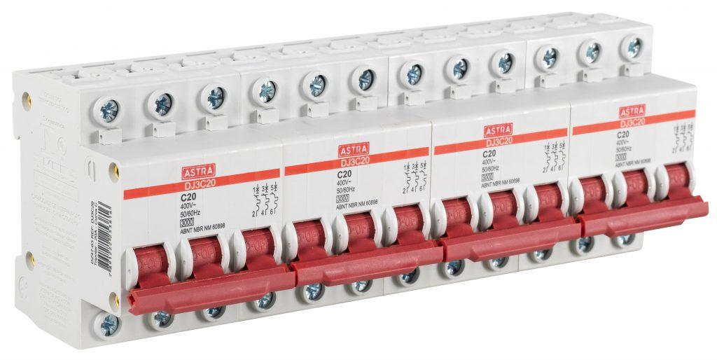 Quatro disjuntores tripolares da Astra aparecem lado a lado. Eles são brancos e possuem botões de acionamento vermelhos.