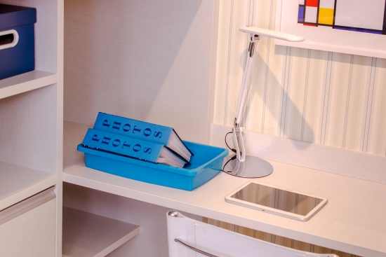 Uma mesa branca acoplada a um armário da mesma cor aparece na imagem. Em cima dela há uma caixa azul com dois álbuns de fotos, uma luminária branca e um tablet branco.