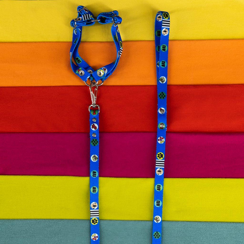 Uma coleira azul com guia está em cima de pedaços de tecidos em diferentes tonalidades.