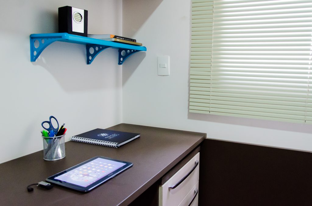 Uma escrivaninha marrom com um tablet, um porta-lápis e um caderno aparecem na imagem. Na parede atrás do móvel há uma prateleira azul com um item de decoração e dois livros.