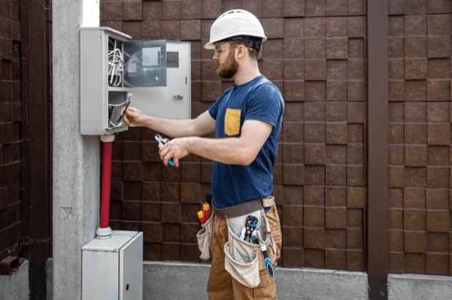 Um homem branco está mexendo em uma caixa de energia em um poste padrão. Ele usa equipamentos de segurança como capacete, óculos e luvas.