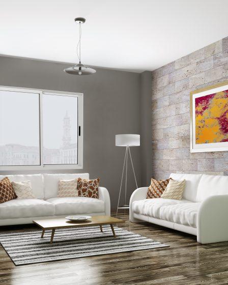 Uma sala de estar com dois sofás brancos e piso de madeira aparece na foto. A parede ao fundo é cinza e possui uma janela de alumínio branca da Astra. A parede do lado direito da imagem parece madeira e possui um quadro colorido. No ambiente é possível ver outros itens decorativos, como uma estante branca, uma mesinha de centro, um tapete e uma luminária.